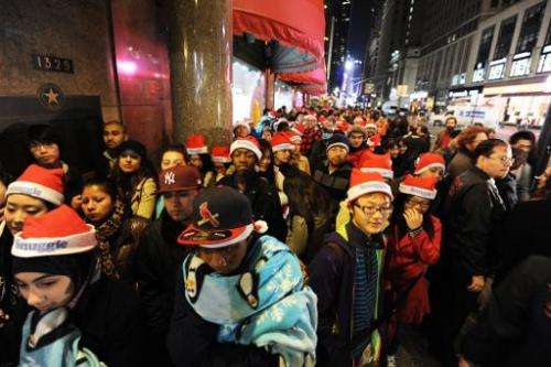This file photo shows people standing in line outside Macy's department store in New York, awaiting the midnight opening to begi
