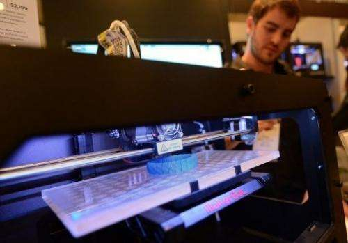 "A visitor looks at a 3D printer at the ""Inside 3D Printing"" event in New York on April 22, 2013"
