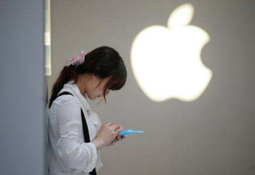 A woman uses her mobile phone outside an Apple store in Shanghai on May 7, 2012