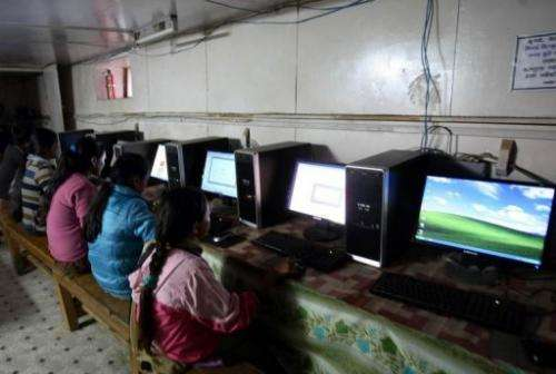 This photo taken on October 25, 2010 shows Nepalese girls surfing the internet in the village of Nagi