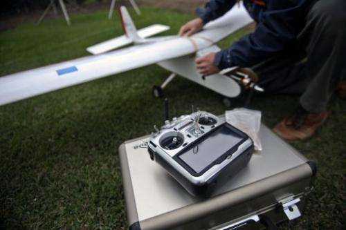 A man prepares a drone before its launch in Lima, Peru on July 10, 2013