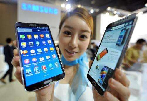 A model holds Samsung's first curved smartphone, the Galaxy Round, at the Electronics and IT Industry Fair in Goyang, north of S