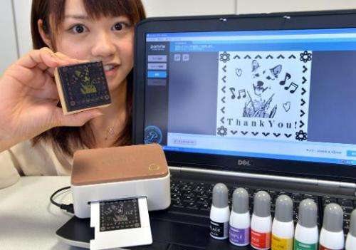 "An employee of Japan's electronics maker Casio Computer displays a stamp maker ""Pomrie"" at the company's headquarters"
