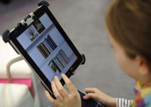 A woman tries out an eBook reader app on an Apple iPad at the Leipzig Book Fair on March 15, 2012 in Germany