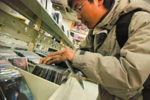 File picture shows a customer looking at pirated DVDs at a shop in Beijing.