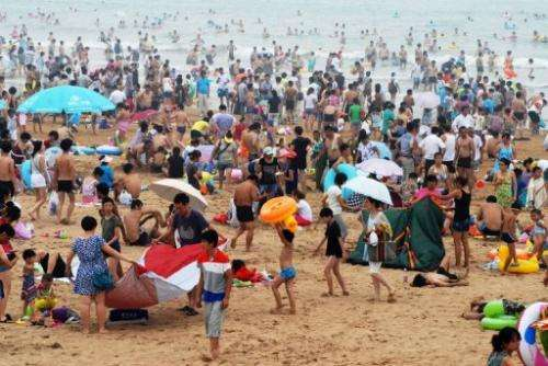 People cool off on a beach in Qingdao, in eastern China, August 11, 2013