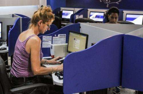People use the internet at a cybercafe in Havana on June 21, 2013