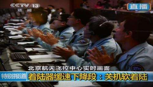 This screen grab taken from CCTV live broadcasting footage shows scientists celebrating at the control centre in Beijing after C