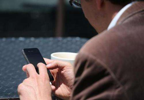 A man uses a smartphone as he sits in Union Square on June 5, 2013 in San Francisco, California