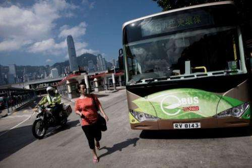 A woman walks past an electric bus in Hong Kong on September 9, 2013