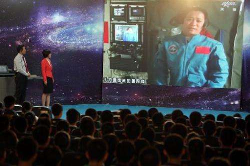 Chinese astrounaut, mission commander Nie Haisheng, speaks to students via video link, gathered at a school in Beijing, of June