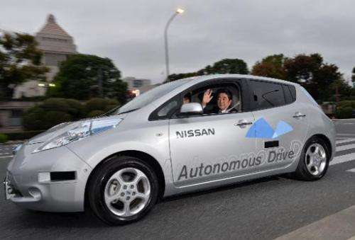 Japanese Prime Minister Shinzo Abe waves during a test drive of Japanese auto maker Nissan Motor's autonomous vehicle in Tokyo o