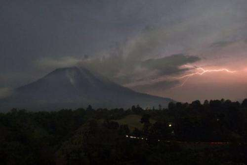Lightning strikes next to Mount Sinabung volcano as it spews steam and ash on September 18, 2013