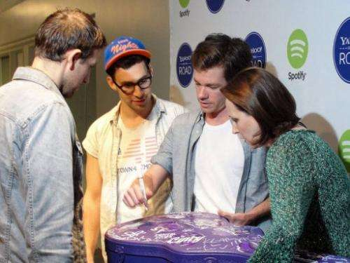 Members of the Grammy-winning band fun. sign a Yahoo music road tour guitar case in San Francisco, May 31, 2013