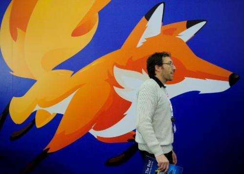 A man walks past a poster of Mozilla Firefox on February 27, 2013 at the Mobile World Congress in Barcelona