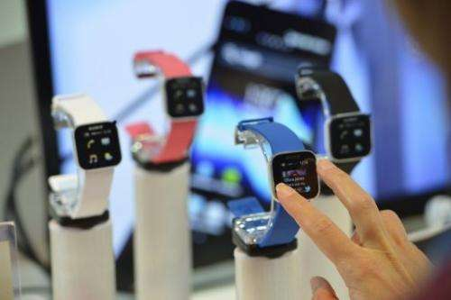 A woman tries out mobile phone and media player watches at the Sony booth at the IFA fair in Berlin on August 30, 2012
