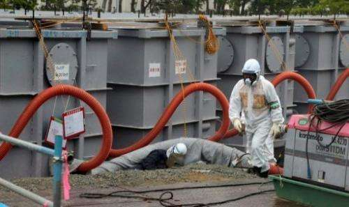 File picture shows a TEPCO worker next  to waste water tanks at Fukushima Daiichi nuclear plant on June 12, 2013