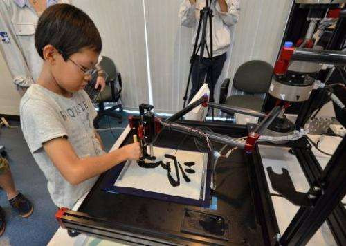 "A boy writes a Chinese letter for ""study"" with a calligraphy robot at Keio University in Yokohama on July 30, 2013"