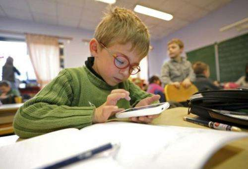 A boy writes on a smartphone during a lesson about Twitter in Seclin, France, on December 11, 2011