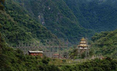 A Buddhist temple sits near an electricity grid main of the Chukha hydro power station, on May 29, 2013