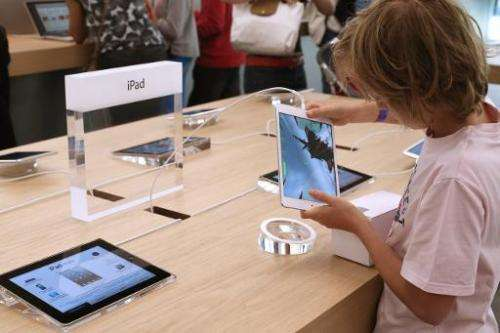 A child plays with an iPad Mini at an Apple store on July 6, 2013 in Rosny-sous-Bois, near Paris