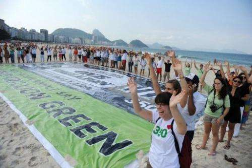 Activists from 350.org and other groups unveil a banner on Copacabana beach in Rio de Janeiro, Brazil on June 17, 2012
