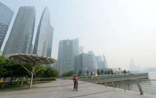A cyclist rides along the pier in front of buildings blanketed by haze in Singapore on June 19, 2013