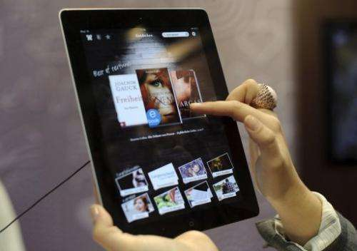 A fair goer tries out the an e-book reader app on an Apple iPad at the Leipzig Book Fair on March 15, 2012