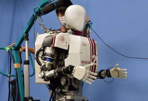"A humanoid robot ""Wabian-2R"", developed by Japan's Waseda University professor Atsuo Takanishi walks for a demonstrati"