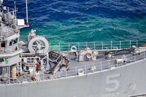 A January 23, 2013 US Navy handout shows a salvage assessment team working aboard USS Guardian