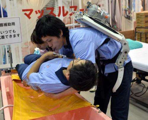 A Japanese elderly care company Asahi Sun Clean employee (top) wearing a power suit, called 'Muscle Suit,' lifts a fellow worker