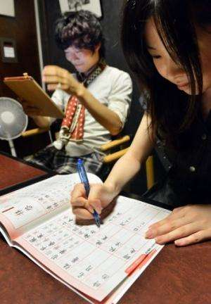 Akihiro Matsumura (L) uses a computer as his friend practices writing Chinese characters in Tokyo on June 19, 2013