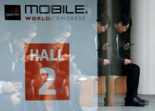 A man looks at his mobile phone during the 2013 Mobile World Congress in Barcelona on February 28, 2013