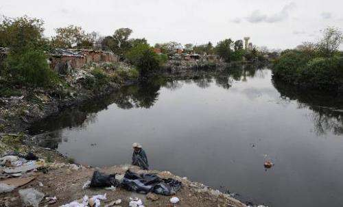 A man of the Villa 21-24 shantytown rummages through garbage on the shore of the Riachuelo in Buenos Aires on October 4, 2011