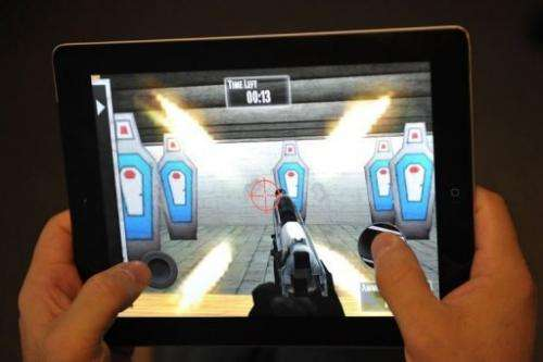 "A man plays the National Rifle Association (NRA) iPhone/iPad app, ""NRA: Practice Range"" on January 15, 2012"