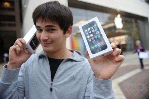 A man poses with his two new Apple iPhone 5S in Glendale, California, September 20, 2013