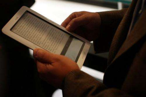 "A man reads an ebook on the ""nook"" digital reader, October 20, 2009 in New York City"