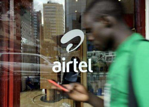 A man with a phone in hand walks past an'Airtel' logo in the Kenyan capital Nairobi on May 20, 2011