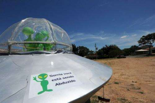 "A mock UFO with a sign reading ""Smile, you are being abducted"" is pictured north of Brasilia, in December last year"