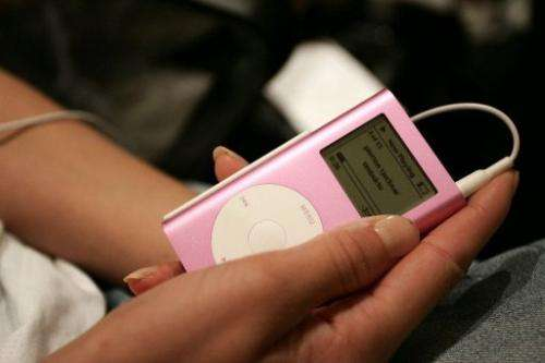 A model listens to music on her iPod backstage during Olympus Fashion Week  in New York on September 15, 2005