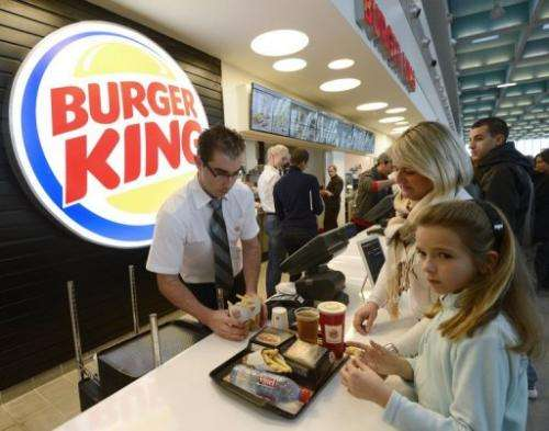 An employee serves customers at the Burger King fast food restaurant in Marseille's airport on December 22, 2012