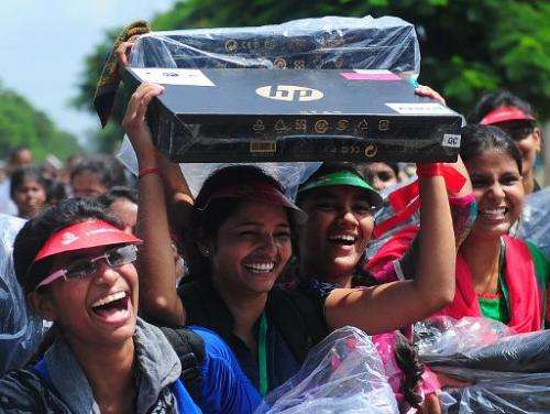 An Indian student holds a Hewlett-Packard laptop given to her by Indian chief minister of Utar Pradesh, Akhilesh Yadav at a cere