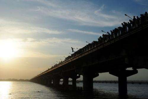 An Indian youth jumps from the from Shashtri bridge into the River Ganges in Allahabad on August 1, 2013
