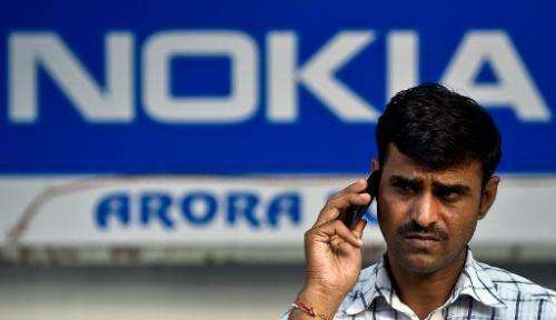 A passer-by talks on his mobile phone outside a Nokia store in New Delhi on October 1, 2013