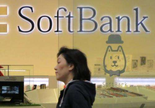 A pedestrian walks past a Softbank logo on display in Tokyo, on June 21, 2013