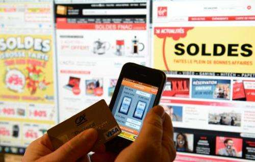 A person holding a credit card and a phone with a sales 'app', in front of websites advertsing for winter sales, on January 9, 2