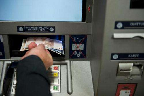 A person takes out Euro banknotes from an automated teller machine at a cash point in Berlin on August 28, 2013