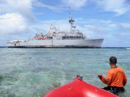 A Philippine coast guard wades towards the USS Guardian trapped on the Tubbataha coral reef, January 22, 2013