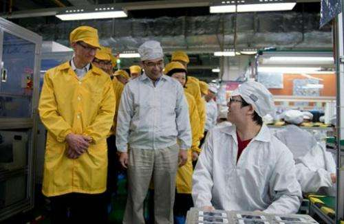 Apple chief executive, Tim Cook (L), visits the iPhone production line in Zhengzhou, on March 28, 2012