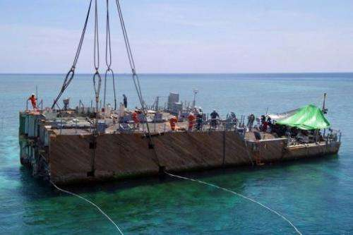 A section of the USS Guardian is lifted from the Tubbataha reef, in western Philippines, on March 30, 2013
